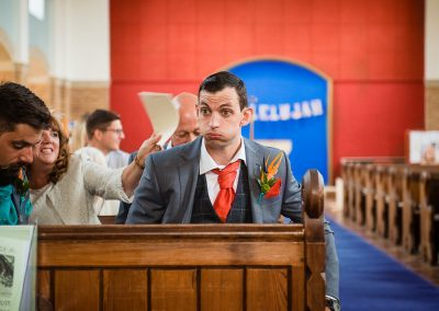 Natural wedding photograph of nervous groom taking deep breaths waiting for bride in Dorset church