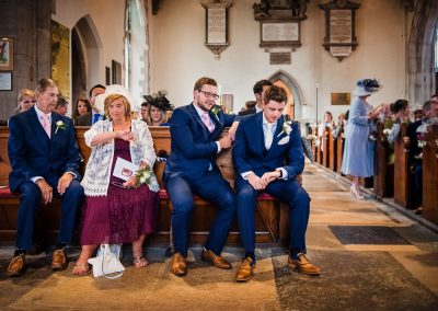 Documentary wedding photo of grooms party waiting in Dorset church checking their watches