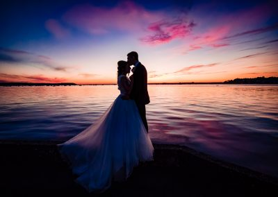 Dorset documentary wedding photograph of bride and groom kissing in silhouette by the sea with blue and orange sunset
