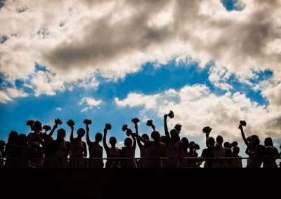 28 bridesmaids silhouetted against cloudy sky waving wedding bouquets on top of a double-decker bus