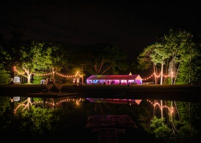 Sopley Lake wedding marquee and festoon lighting reflected at night in lake surface