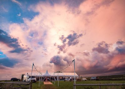 Spectacular blue and pink storm clouds above countryside wedding marquee