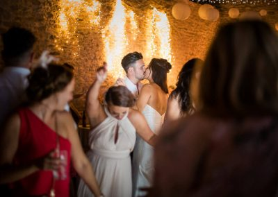 Stunning documentary wedding photograph of bride and groom kissing on wedding dancefloor