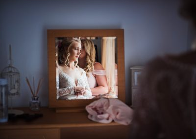 Beautiful bride in detailed wedding dress reflected in mirror on wedding morning