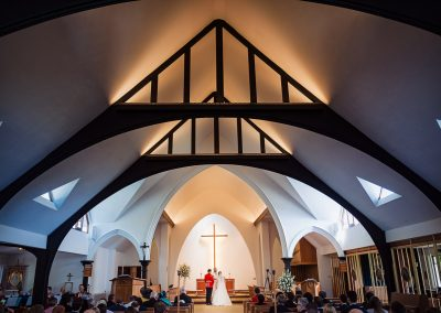 Symmetrical dark wooden church roof above military wedding ceremony