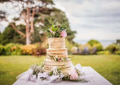Three tier butter iced naked sponge wedding cake decorated in flowers
