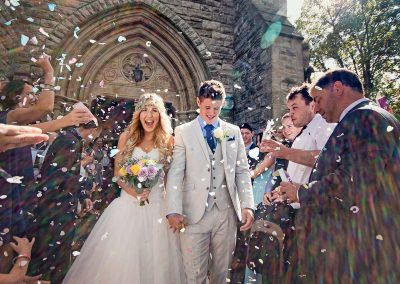 Excited bride and groom leave church in a shower of confetti and sunlight