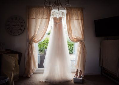 Photo of stunning backlit wedding dress hanging in the window