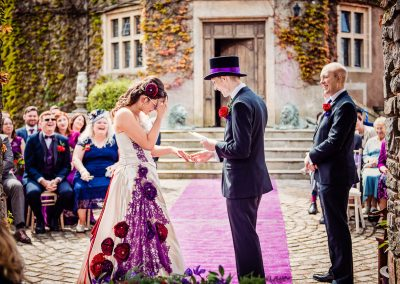 Bride in purple flower dress holds her head in hand during wedding vows at Walton Castle