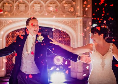 Backlit bride and groom show off first dance moves with red love heart confetti