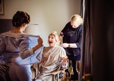 Documentary wedding photo of bridesmaid flashing bride as her hair is styled on wedding morning by one thousand words photography