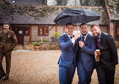 Documentary wedding photograph of laughing wedding guests under umbrella drinking beer