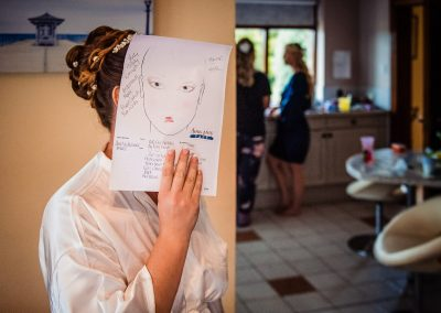 Bride holds wedding make up drawing over her face on wedding morning documentary wedding photo by one thousand words