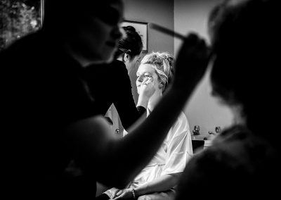 Black and white documentary wedding photo of bride and mother having makeup applied photo by one thousand words