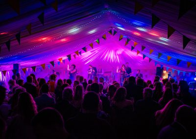 Wedding disco party band with coloured lighting in marquee with bunting
