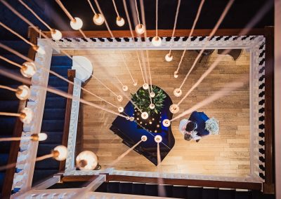Bride and groom photographed from above with piano and square staircase at Blamer Lawn Hotel by one thousand words wedding photography
