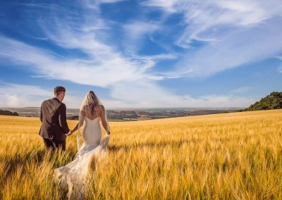 Bride and groom walk sunny Dorset countryside golden field photo by one thousand words wedding photographers