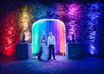 Bride and groom stand hand in hand outside Walton Castle wedding venue at night with rainbow lighting