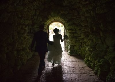 Bride and groom walk through stone tunnel at Italian Villa in Dorset