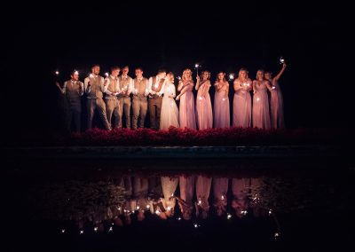 Wedding party with night time sparklers at Italian Villa lake with reflection