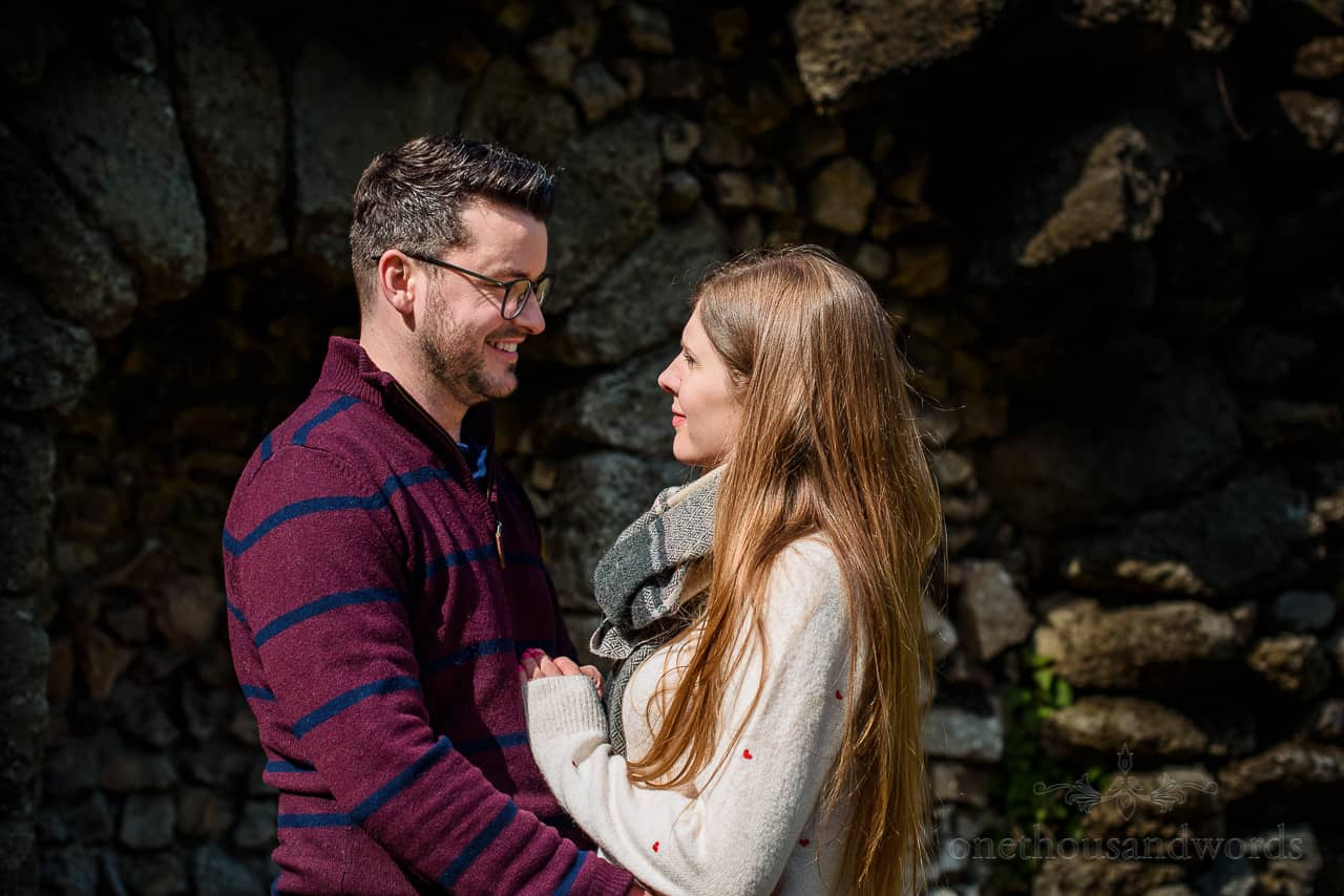 Engagement shoot couple look into each others eyes in front of stone grotto in shadow