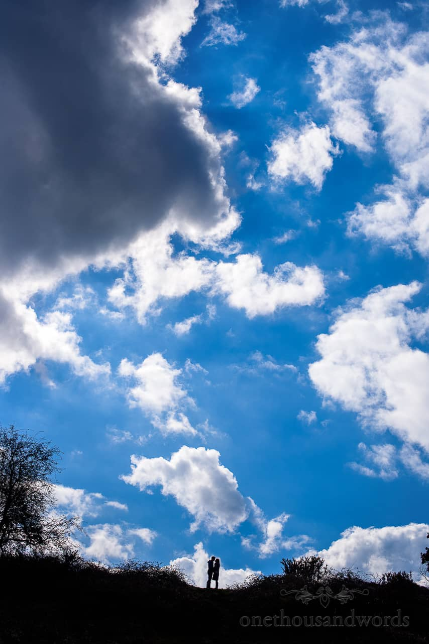 Couple kissing in silhouette against cloudy blue sky