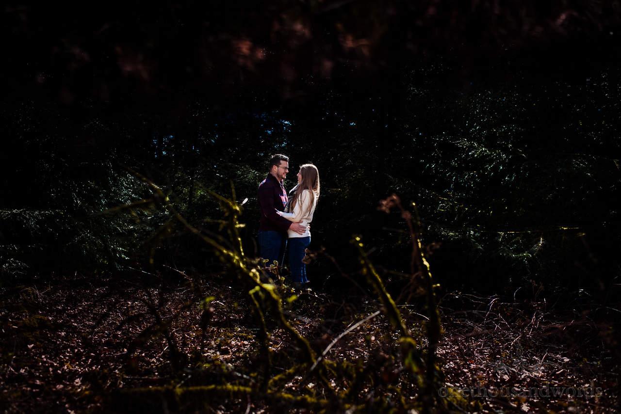 Engaged couple photo shoot in woodland shadows