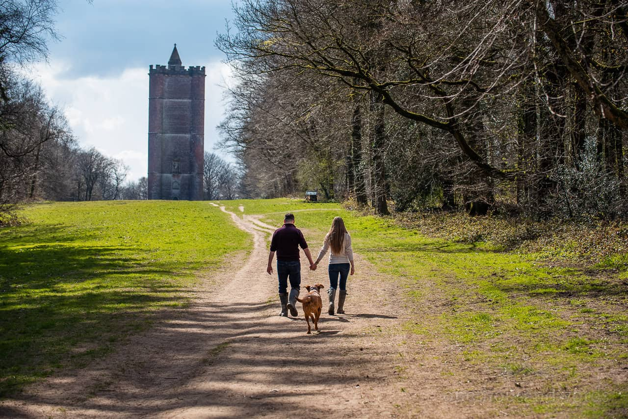 King Alfred's Tower engagement photos of couple walking through trees followed by pet dog