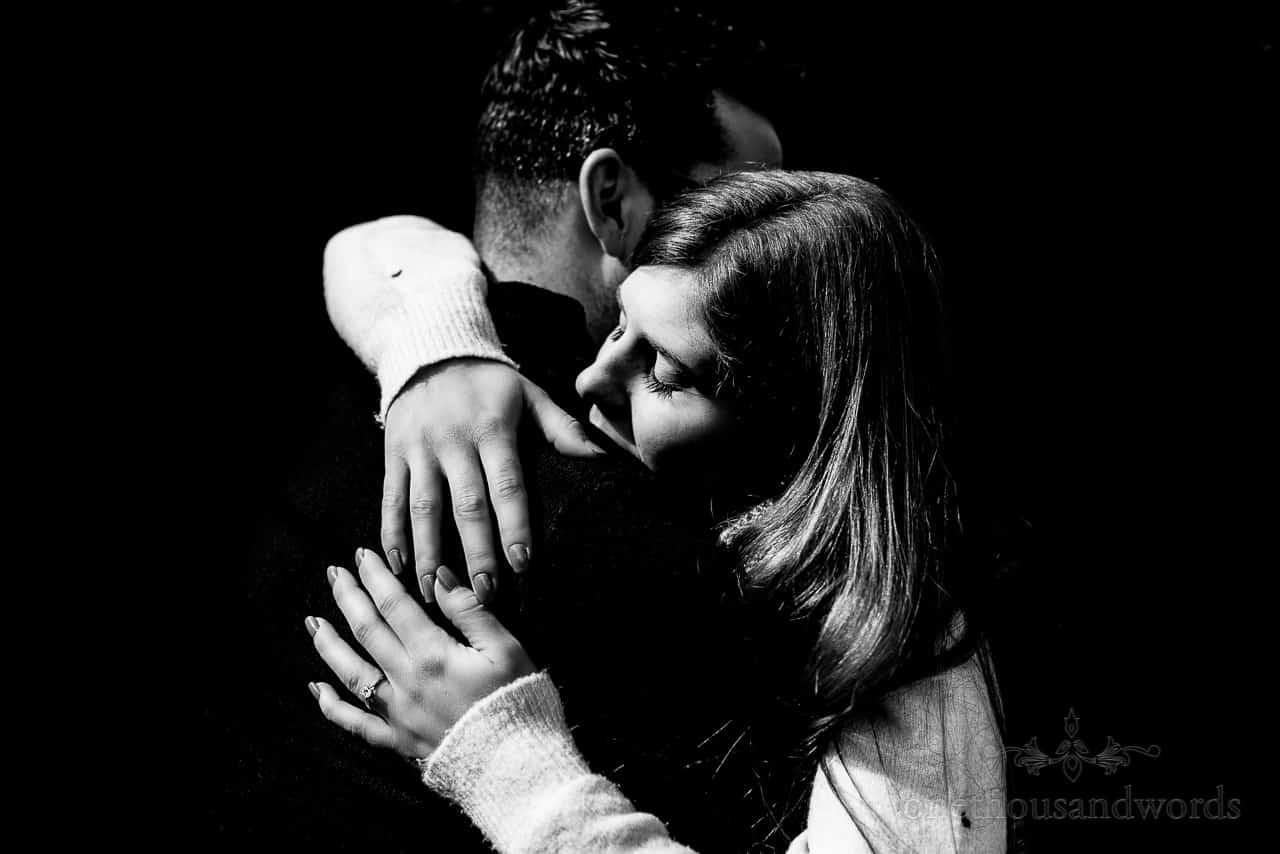 Emotional hug black and white photo of couple with diamond engagement ring