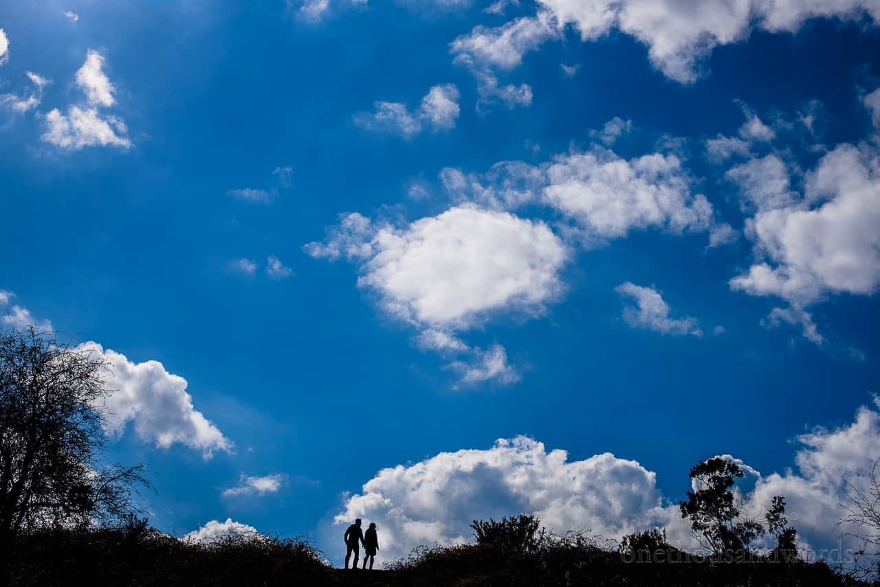 Silhouette of couple walking in countryside against blue cloudy sky