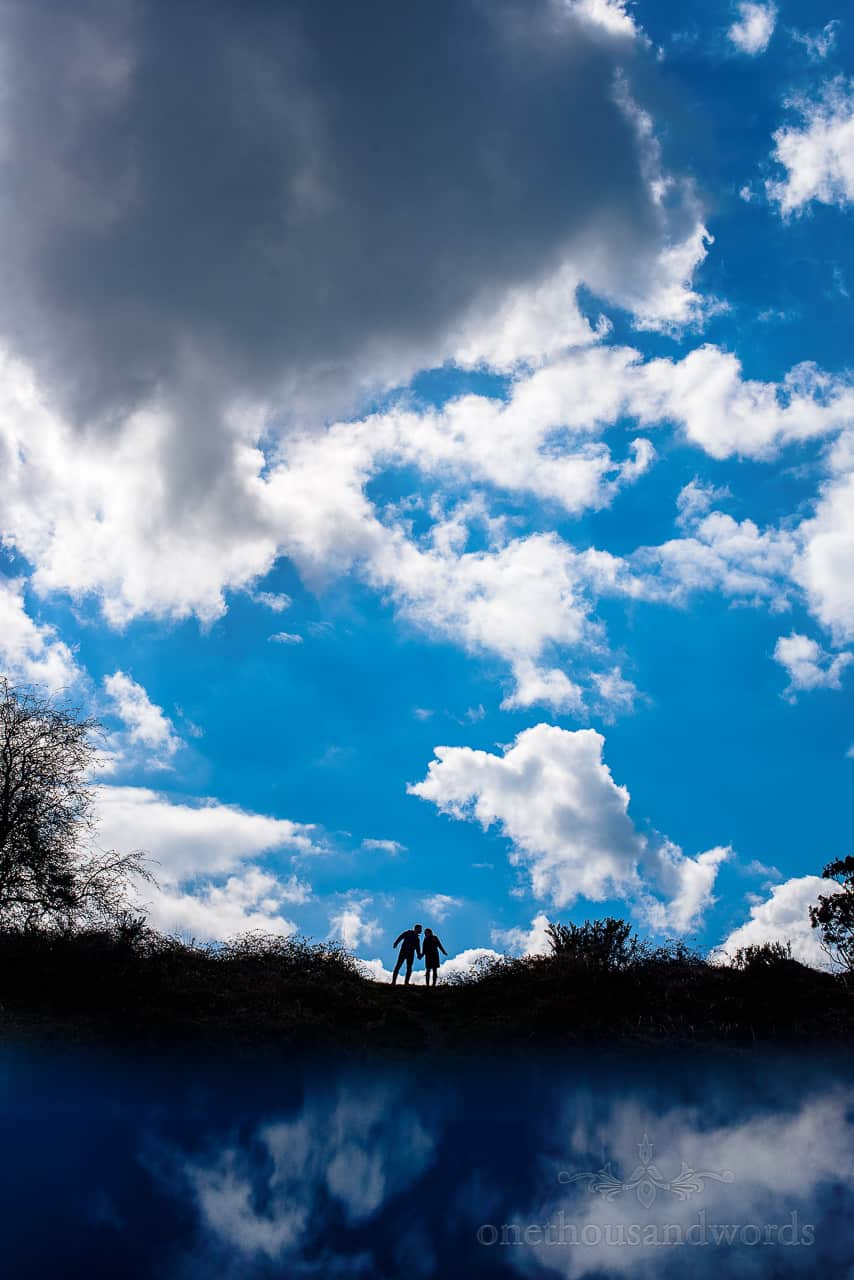 Engagement photo of kissing couple silhouette against cloudy blue sky reflection
