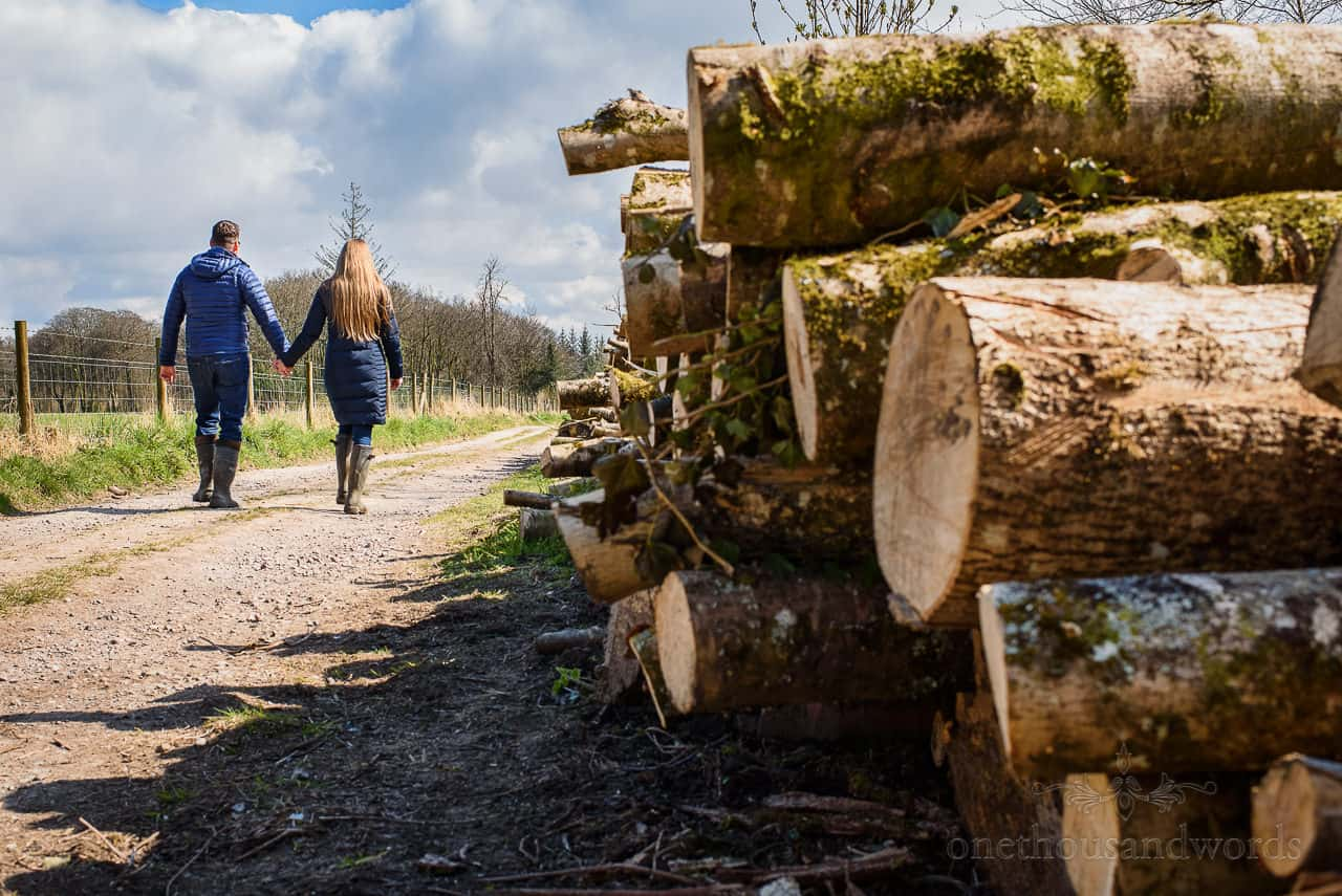 bride and groom to be walk hand in hand past rural log pile