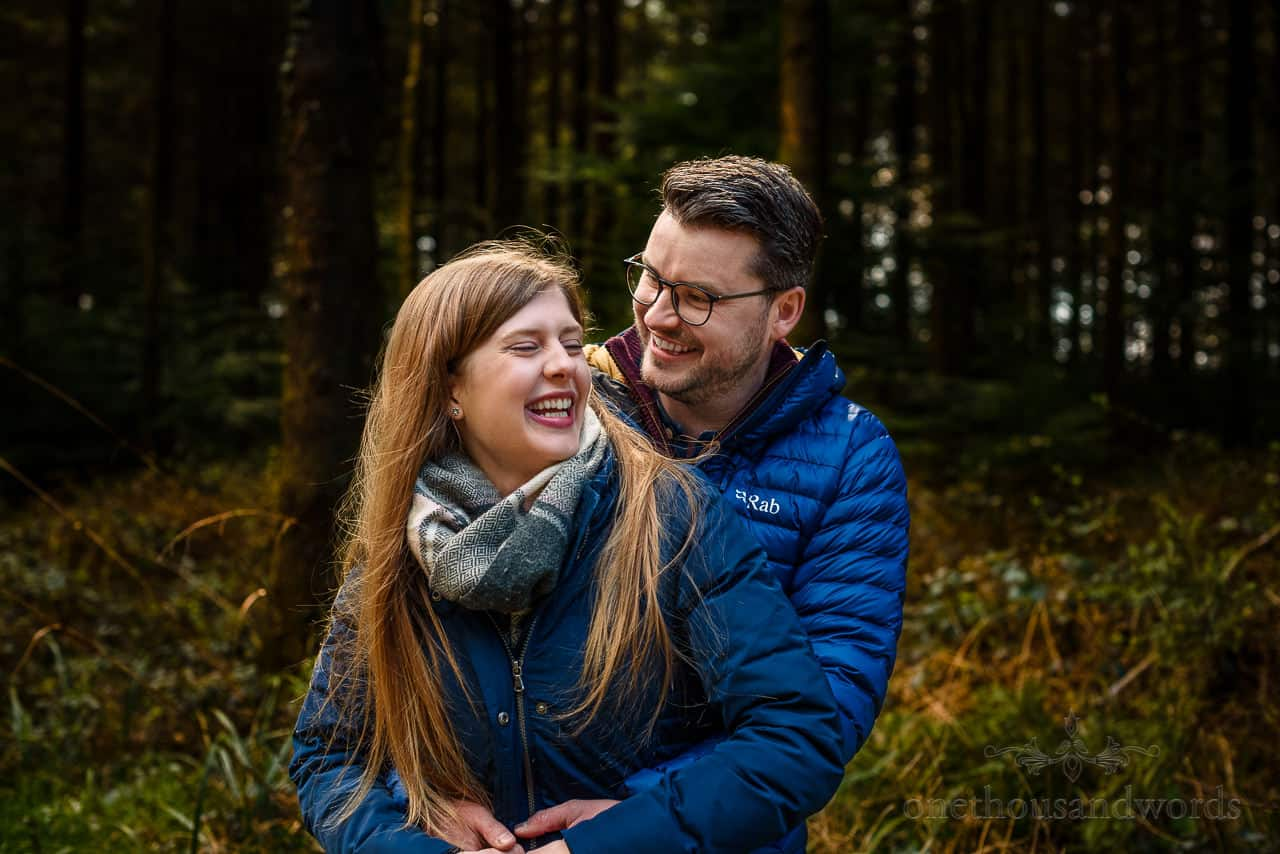 King Alfred's Tower engagement shoot couple laughing in blue jackets in Wiltshire woodland