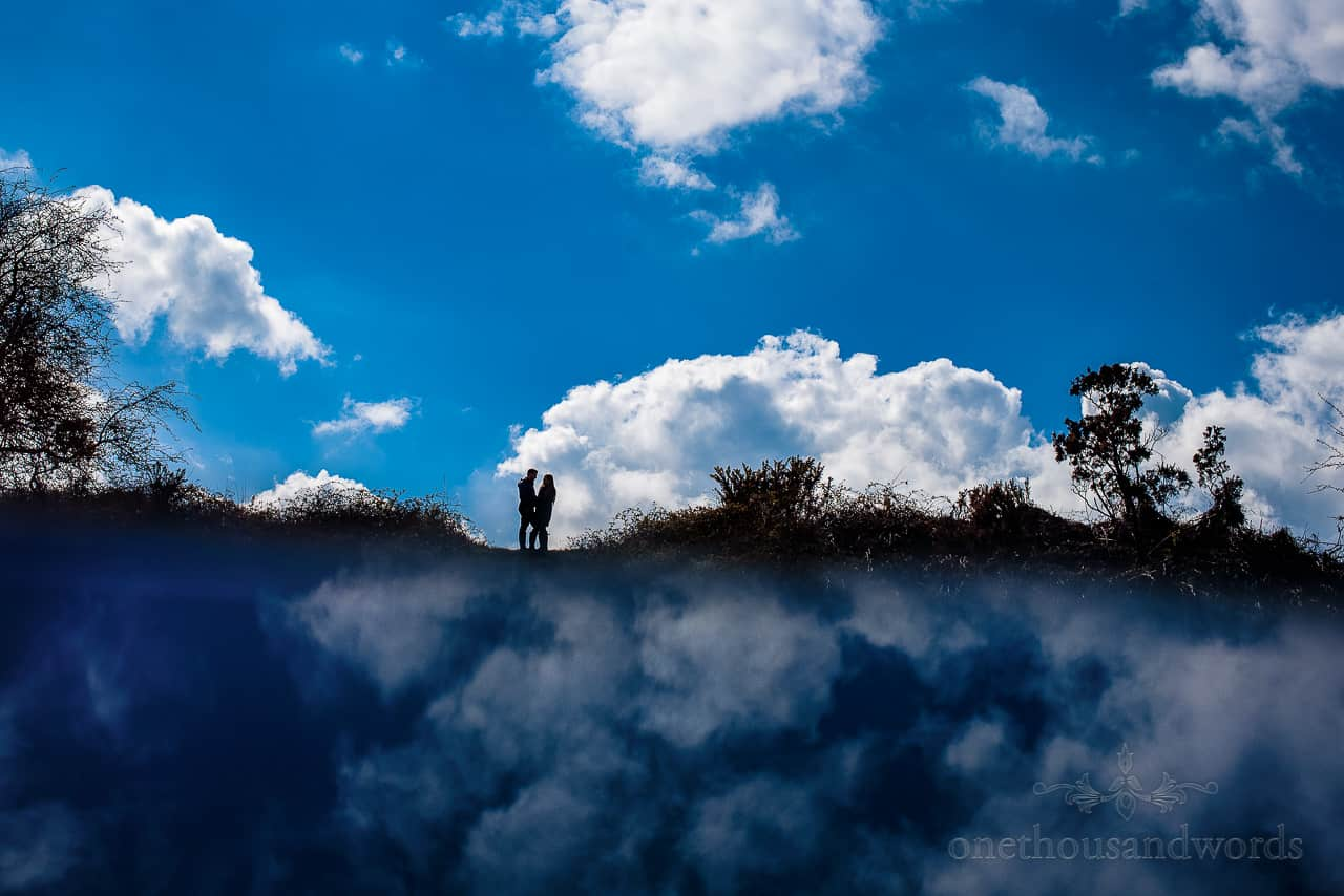 Bride and groom to be in silhouette against blue cloudy sky reflection
