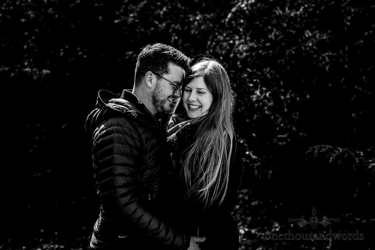 Black and white engagement photograph of laughing couple hugging