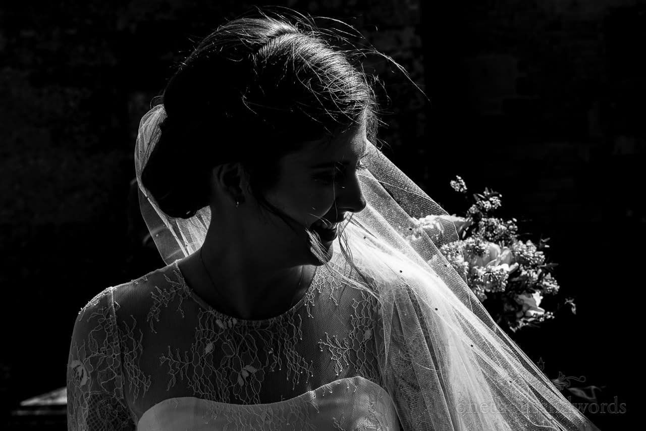 Black and white backlit bridal portrait photograph with glowing veil