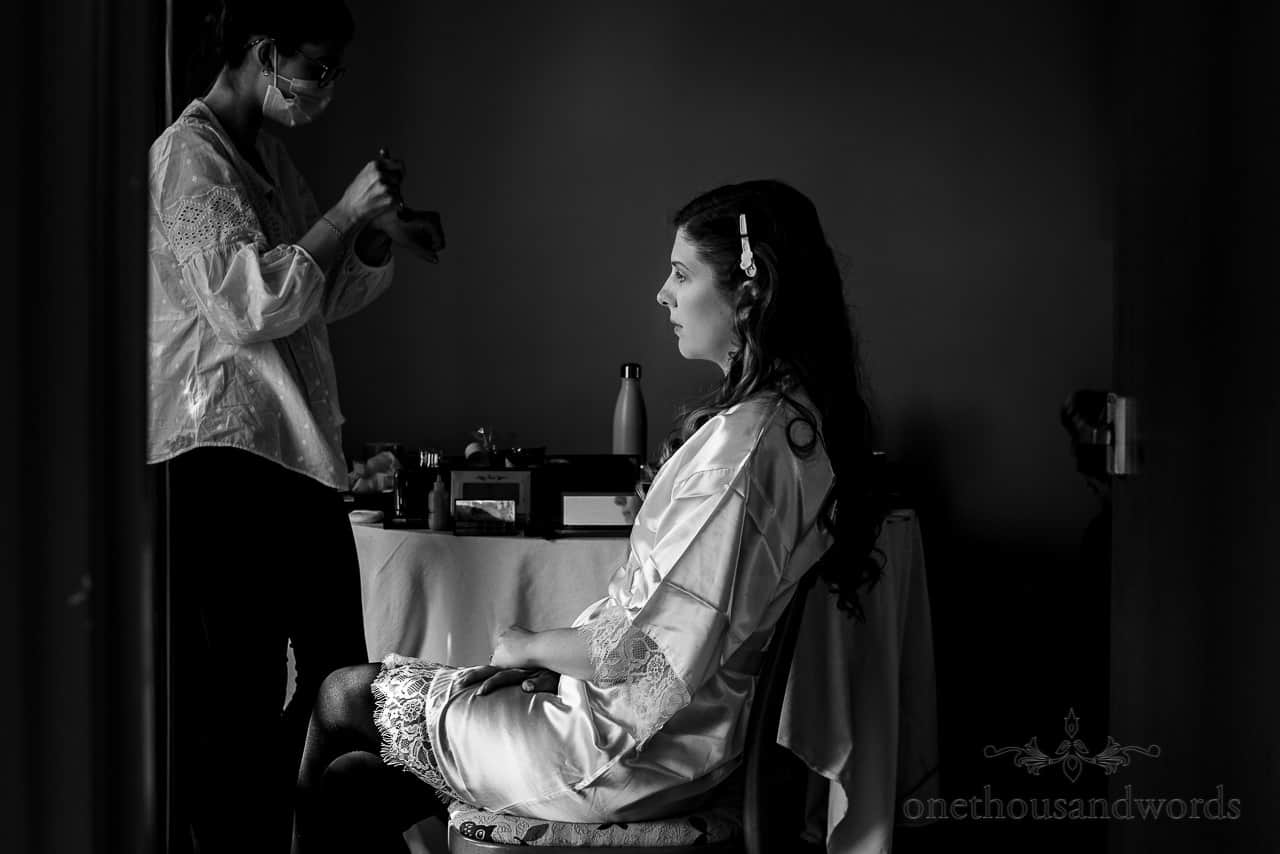 Black and white photograph of bridal preparation with makeup artist