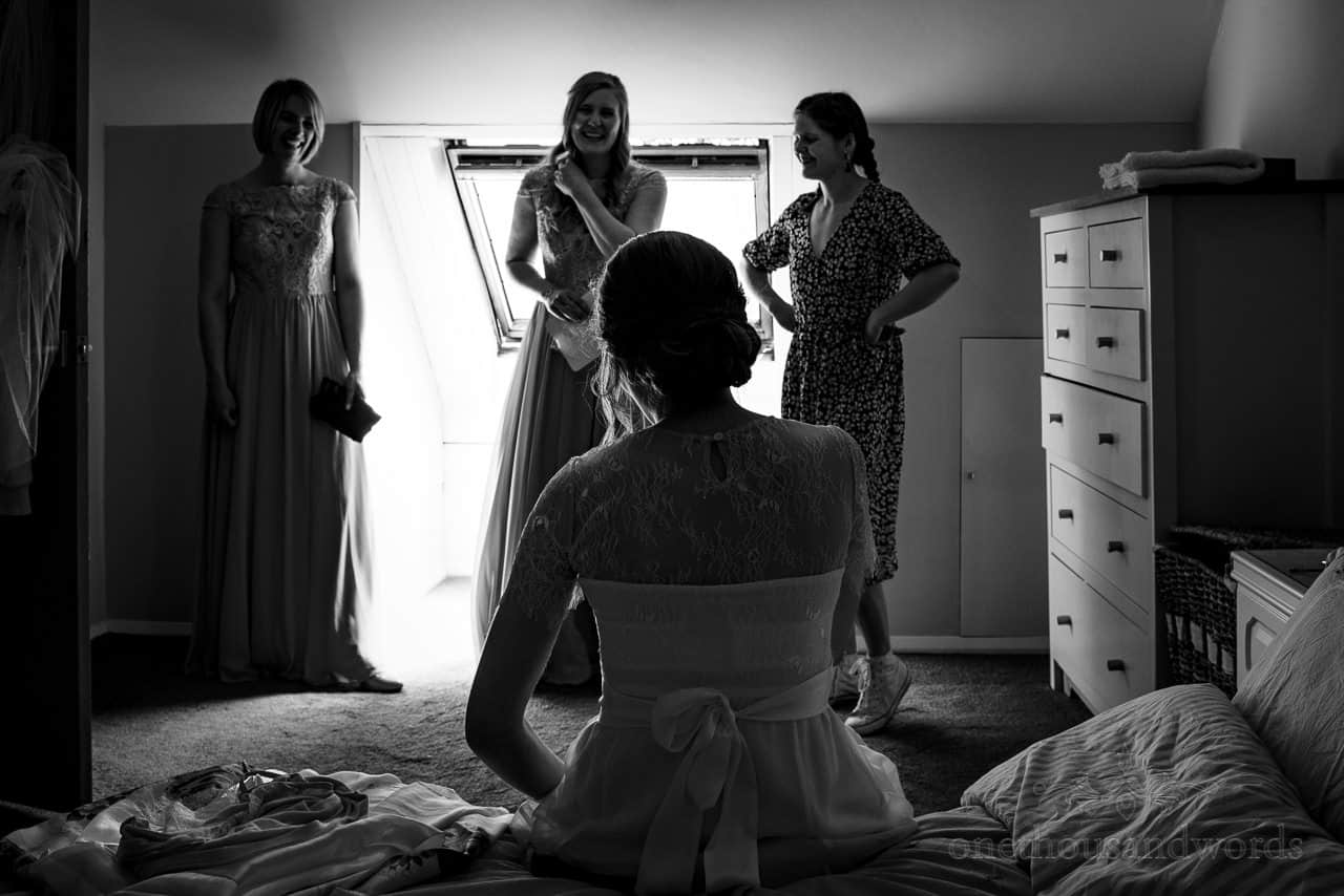 Black and white documentary wedding photo of bride sat on bed watched by laughing bridesmaids