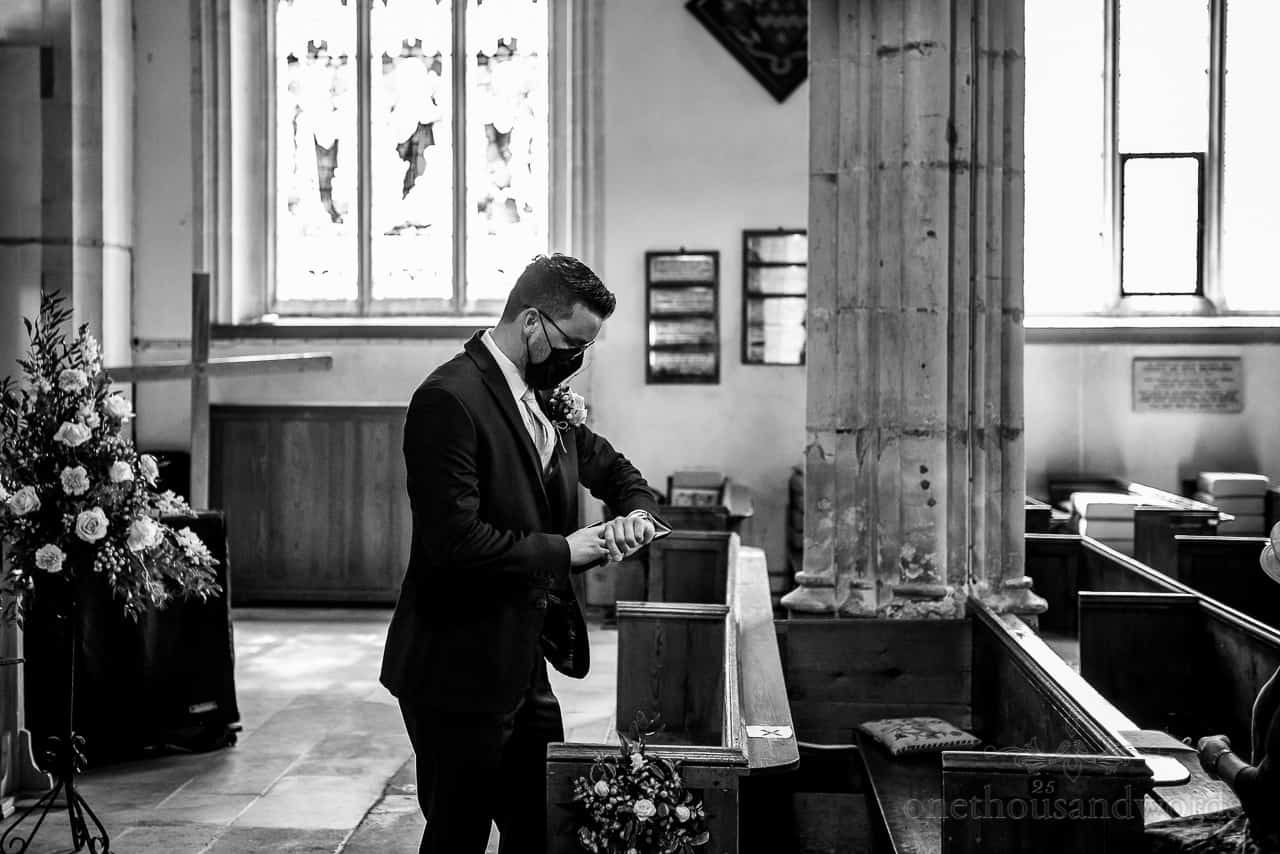 Black and white photo of nervous groom in COVID mask checking his watch in church wedding venue