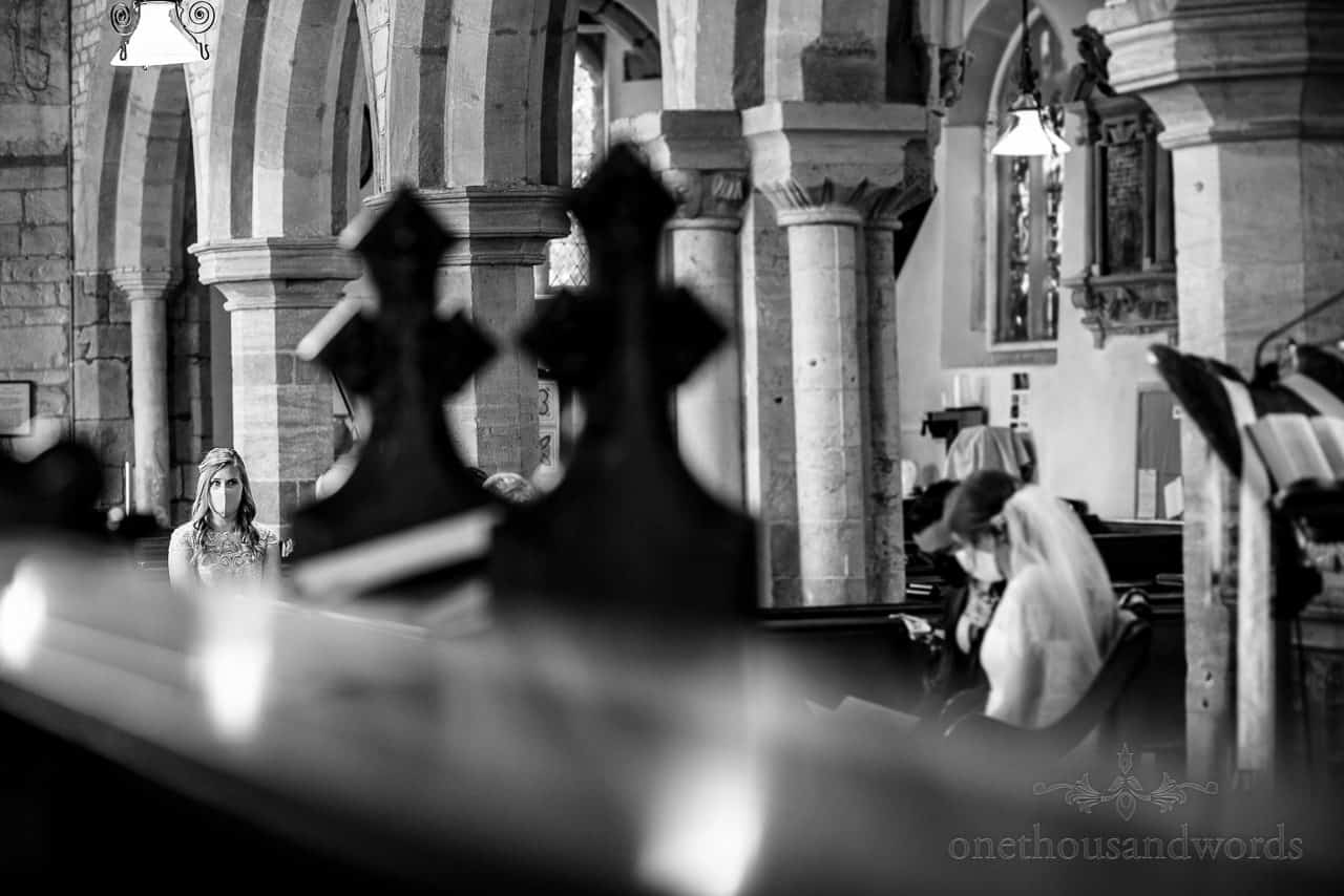 Black and white photo of bridesmaid in COVID mask watching church wedding ceremony