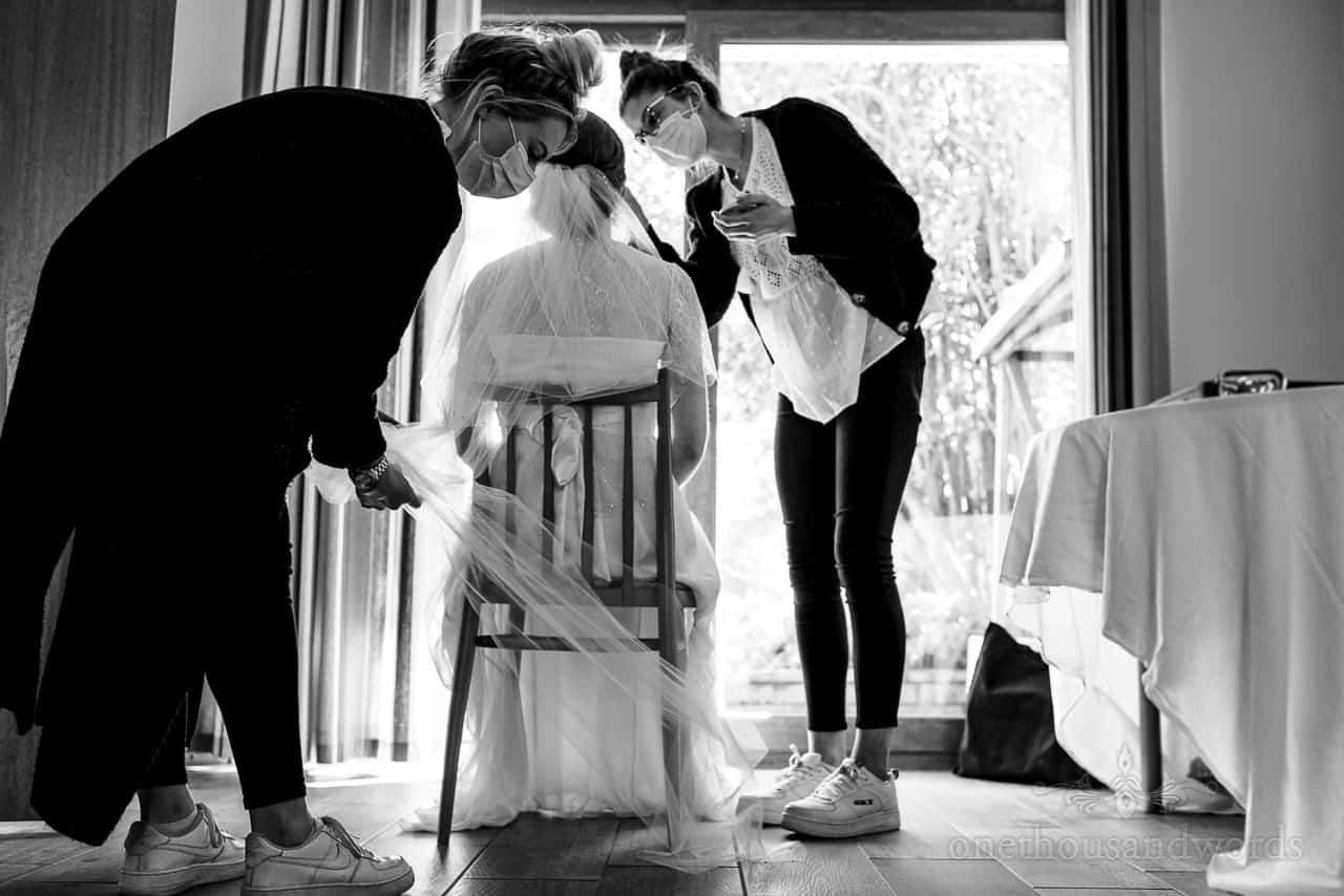 Documentary black and white wedding photograph of makeup artist and hair stylist working on the bride