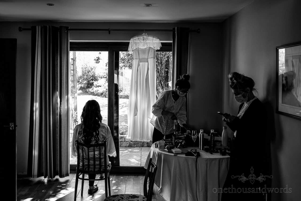 Black and white wedding photograph of bride waiting to have wedding makeup styled on wedding morning