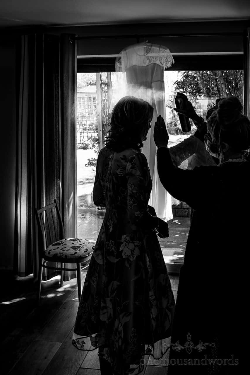Black and white silhouette photo of mother of the bride having wedding hair sprayed