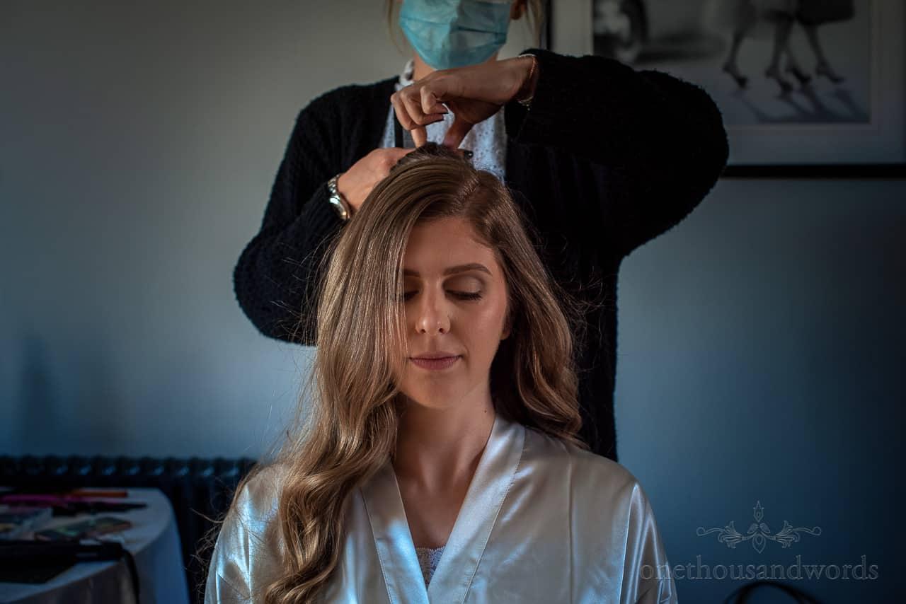 Calm blonde bride has wedding morning hair styled