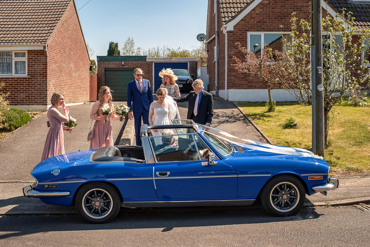 Bridal party outside family home surrounds blue triumph stag open top wedding car