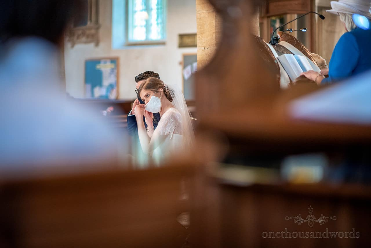 Documentary wedding photograph of bride adjusting COVID mask during church wedding ceremony readings.