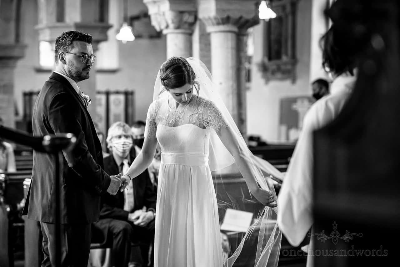 Black and white documentary wedding photo of bride adjusting her veil at church wedding ceremony