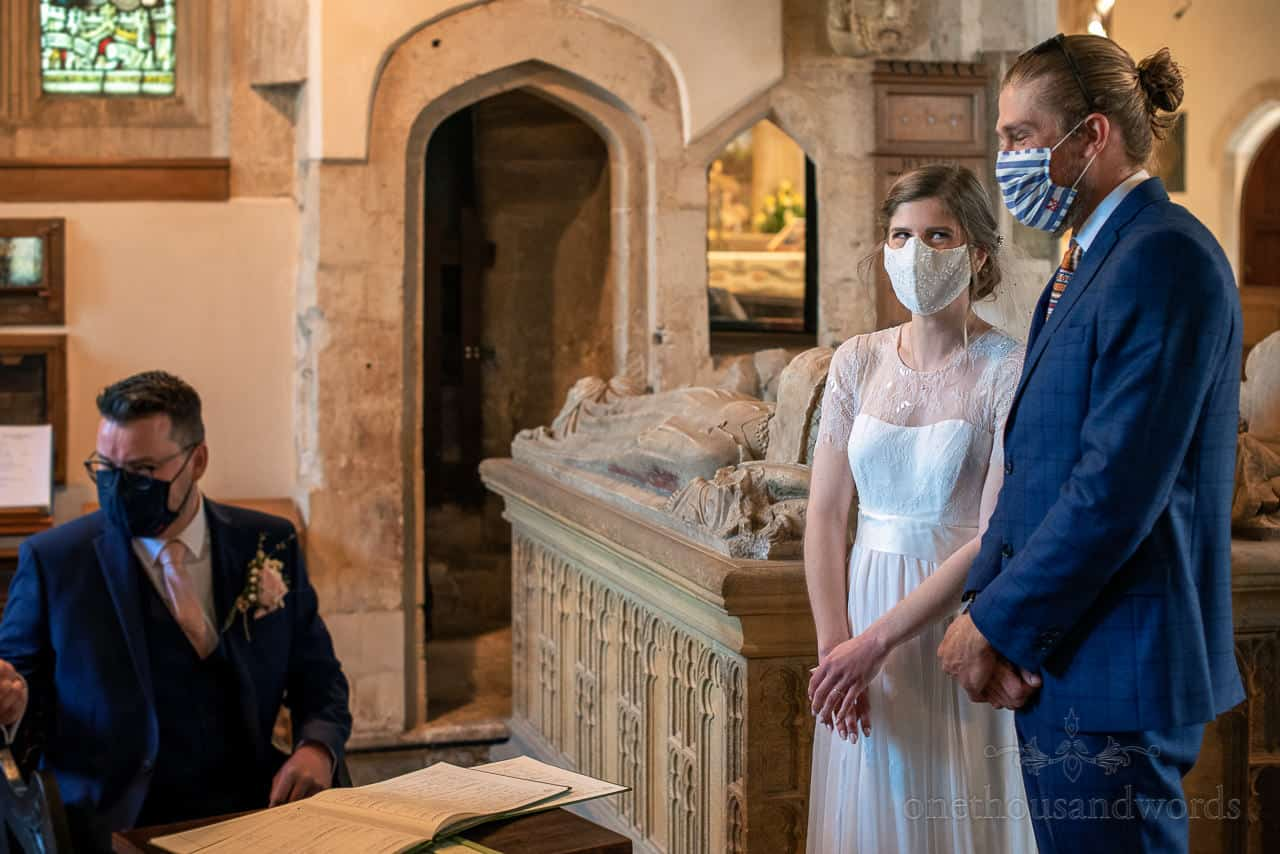Bride laughs at brother behind COVID mask whilst groom signs marriage register in church