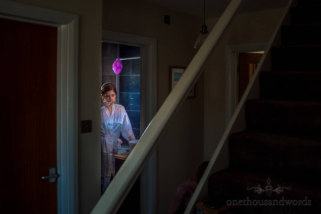 Bride brushes her teeth in bathroom with unusual lighting on wedding morning
