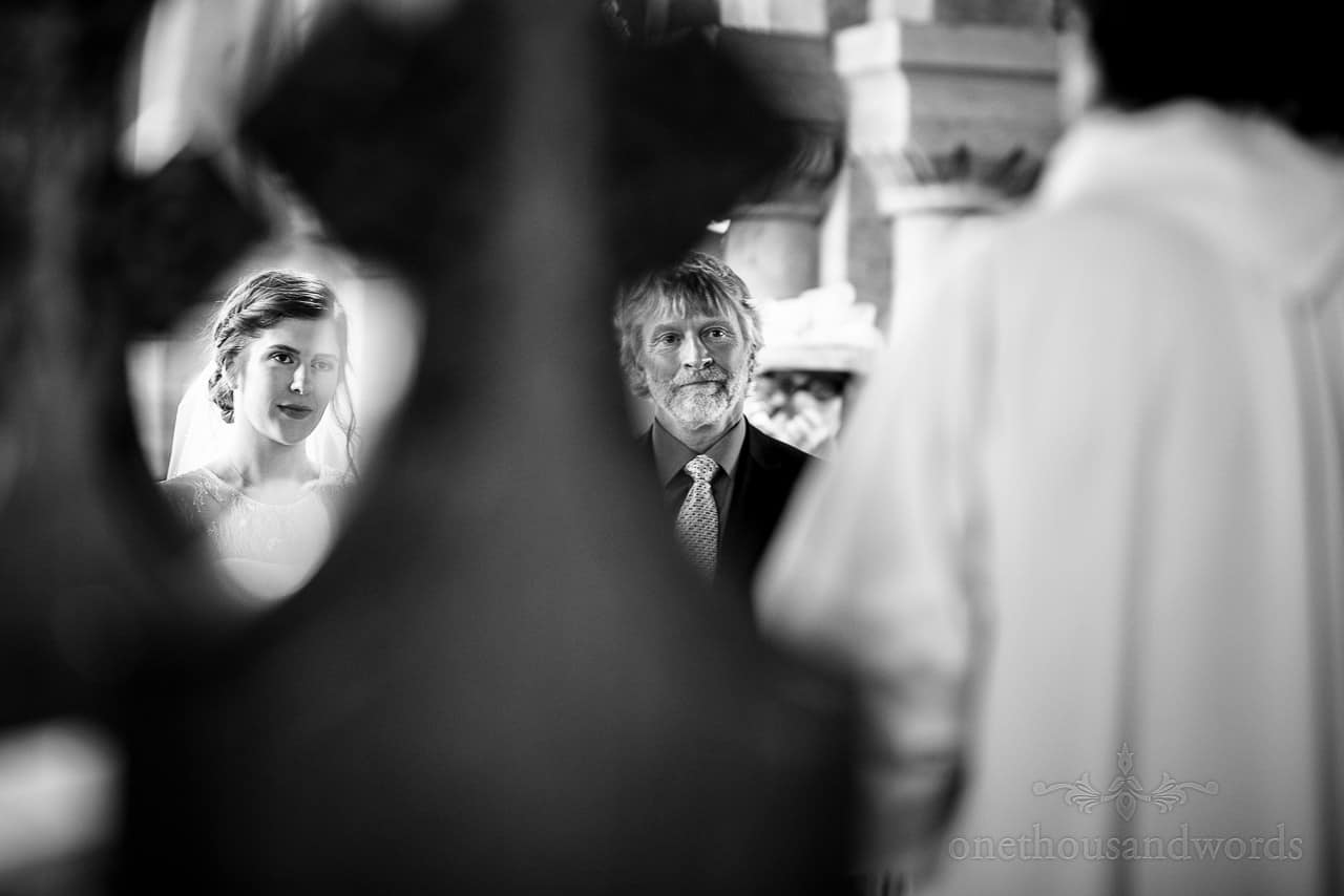 Black and white wedding photograph of bride and father's faces taken through church pew